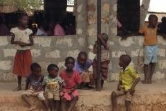 Kinder vor einem neuen Klassenbau. Hier fehlt noch der Verputz